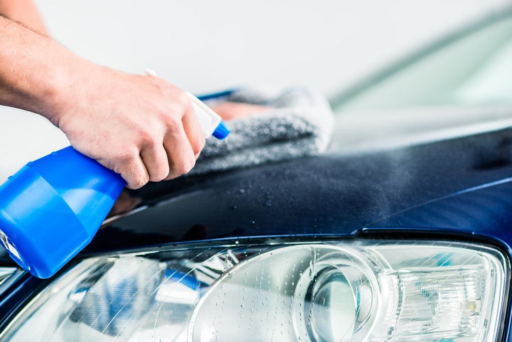 Man cleaning car with car care products